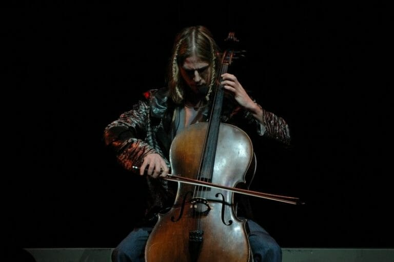 T, who is the member of famous band from Canada and he is playing violin with the help of bow.